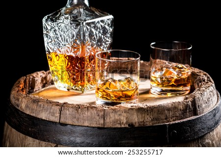 Two glasses of aged whiskey or brandy on the rocks - stock photo