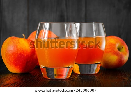 Two glasses of Apple juice and apples on wooden table. Selective focus - stock photo