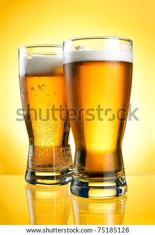 Two glasses of beer close-up with froth over yellow background - stock photo