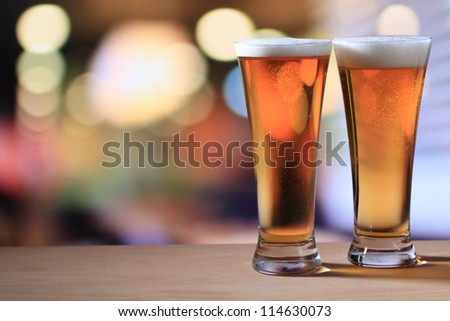 Two glasses of beer on a table - stock photo