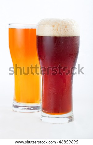 two glasses of beer on a white background - stock photo
