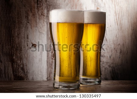 two glasses of beer over vintage wood background - stock photo