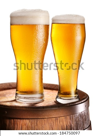 Two glasses of beer over woden barrel. File contains clipping paths.  - stock photo