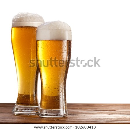 Two glasses of beers on a wooden table. Isolated on a white background. - stock photo