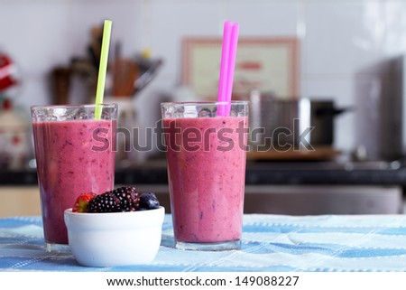 Two glasses of berries smoothies topped with dried fruits and nuts, blue cloth towel - stock photo
