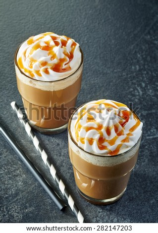 two glasses of caramel latte with whipped cream on dark table - stock photo