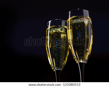 Two Glasses of Champagne against Dark Background - stock photo