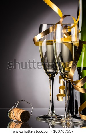 Two glasses of champagne and bottle with serpentine - stock photo
