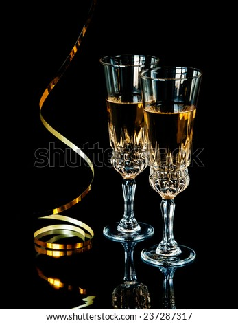 Two glasses of champagne and golden serpentine on a black background - stock photo