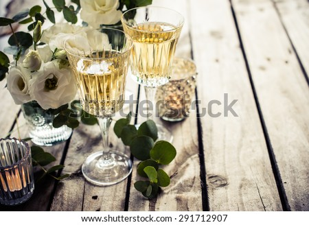 Two glasses of champagne and white flowers, candles on an old vintage rustic wooden table. Vintage summer wedding table decoration. Festive decor. - stock photo