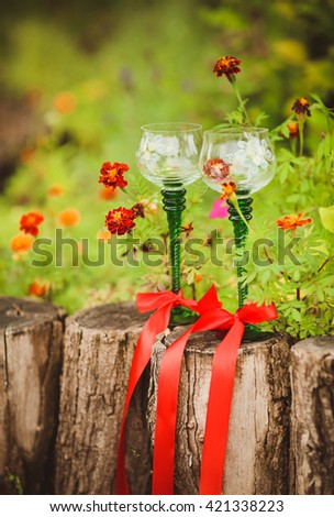Two glasses of champagne decorated with flowers. - stock photo