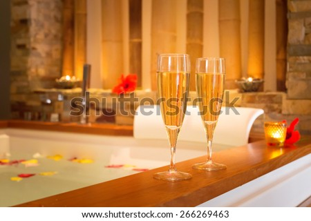 Two glasses of champagne near jacuzzi in a warm tone. Shallow DOF - stock photo