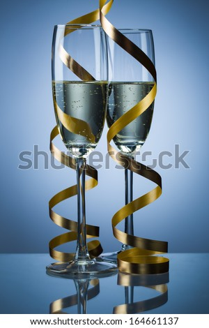 Two glasses of champagne on light blue background - stock photo