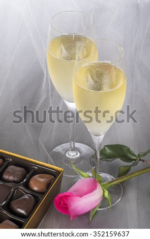 Two Glasses of Champagne, Single Pink Rose and an Open Box of Gourmet Chocolates - stock photo