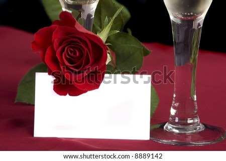 Two glasses of champagne with a rose and white card - stock photo