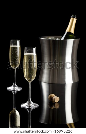 Two glasses of champagne with a stainless bucket in the background isolated on a black background - stock photo