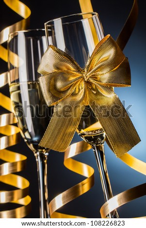 Two glasses of champagne with bow on blue background - stock photo