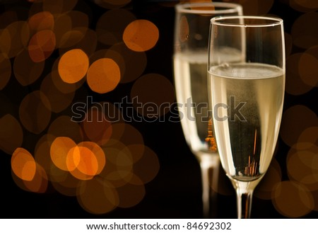 Two glasses of champagne with golden bokeh - stock photo
