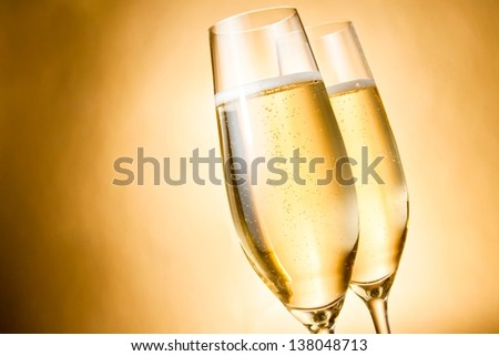 two glasses of champagne with golden bubbles against golden background - stock photo