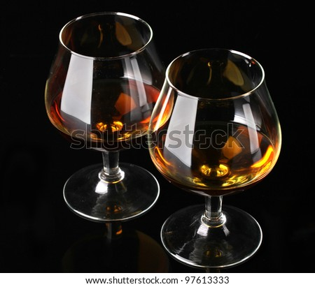 Two glasses of cognac on black background - stock photo