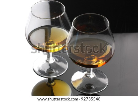 Two glasses of cognac on grey background - stock photo