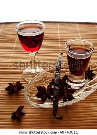 two glasses of cordial with stars of anise and vanilla - stock photo