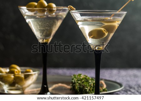 Two glasses of Dry Martini, classic cocktail with olives, vodka and gin served cold - stock photo