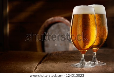 Two glasses of fresh foamy beer on a table in a vintage beer cellar with a barrel in the background - stock photo