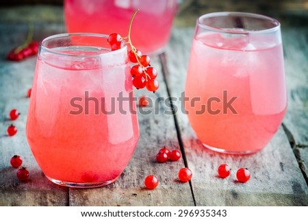 two glasses of homemade red currant lemonade on wooden table - stock photo