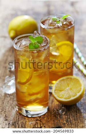 two glasses of iced tea with lemon on wooden table, selective focus - stock photo
