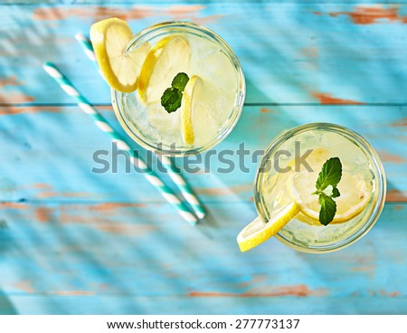 two glasses of lemonade shot from overhead view on rustic table top - stock photo