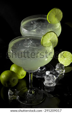 Two glasses of margarita cocktail on a black background. - stock photo