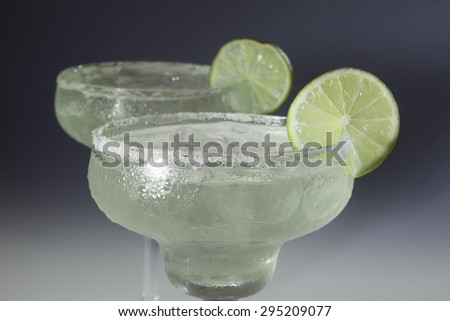 Two glasses of margarita cocktail on a dark background. - stock photo