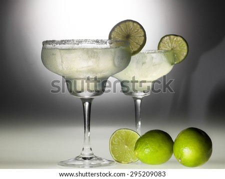 Two glasses of margarita coctail on black and white background with deep shadows. - stock photo