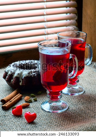 two glasses of mulled wine with red hearts on old wooden table against the background of blinds  - stock photo