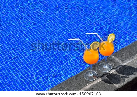 Two glasses of orange juice by the swimming pool -- Vacation Concept  - stock photo
