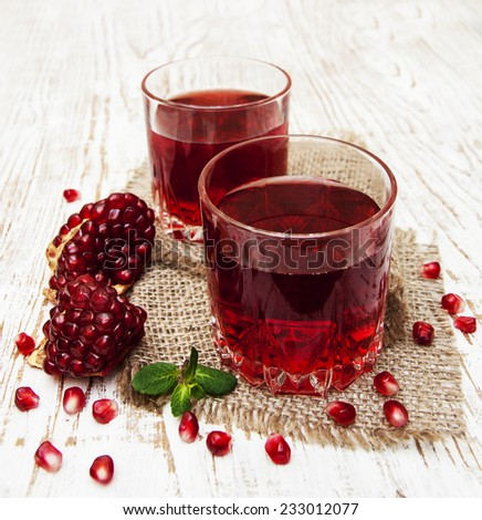 Two glasses of pomegranate juice with fresh fruits on wooden table - stock photo