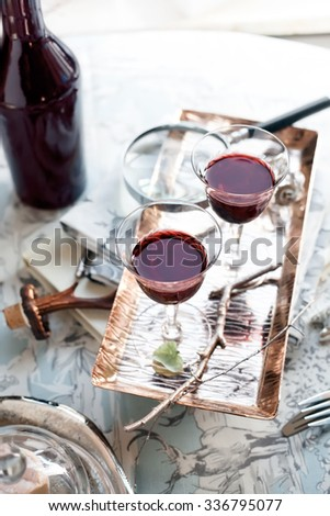 Two glasses of port wine/sherry set with classic style accessories. Retro/classic/imperial style accessories. Natural light photo. Shallow focus. Toned photo. - stock photo