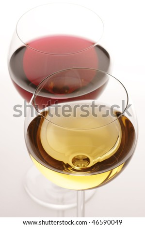 Two glasses of red and white wine close-up on light background. - stock photo