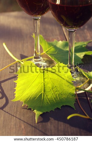 Two glasses of red wine and grape leaves on a wooden surface in beams of the setting sun - stock photo