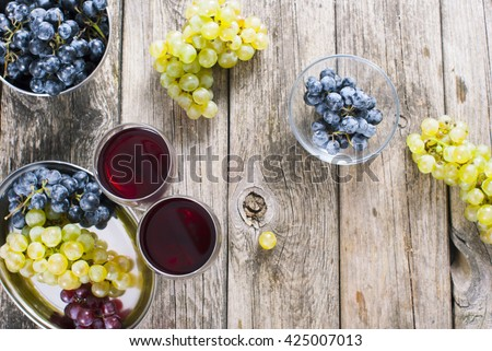 two glasses of red wine and grapes at bowls on old wooden table - stock photo