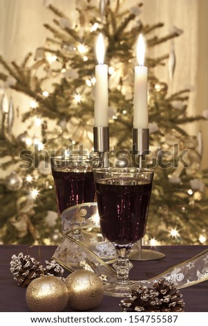 Two glasses of red wine with candles - stock photo