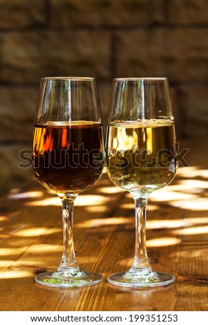 Two glasses of sherry on a wooden table. - stock photo
