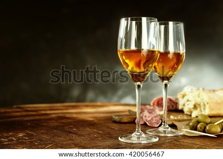 Two glasses of sherry served with tasty traditional Spanish tapas of olives, salami and fresh bread on an old wooden table with copy space - stock photo