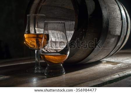 Two glasses of strong alcohol, near the oak barrel - stock photo