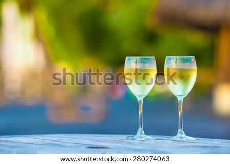 Two glasses of tasty white wine at sunset on wooden table - stock photo