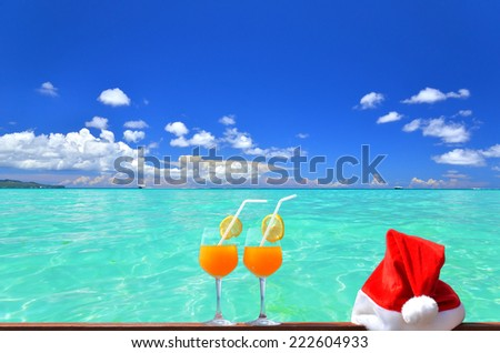 Two glasses of tropical fruit juice and red santa hat near the beautiful tropical sea  - stock photo