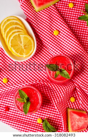 two glasses of watermelon drink with mint on red cloth - stock photo