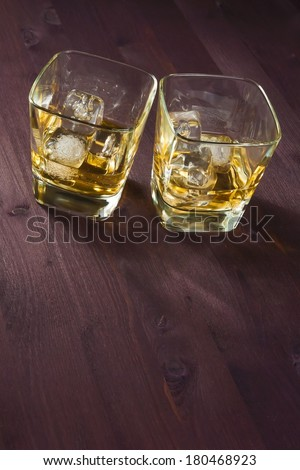 two glasses of whiskey on old wood background - stock photo