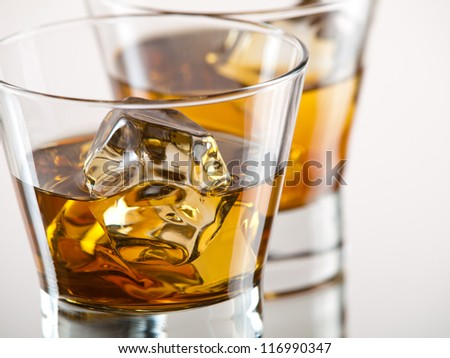 Two glasses of whiskey on the rocks - stock photo